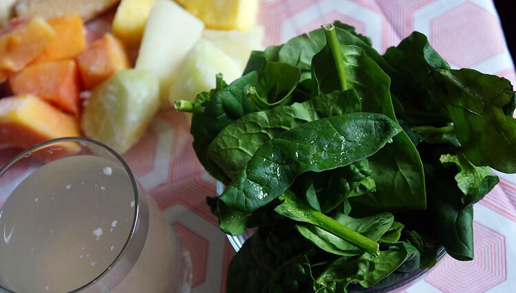 Island Green Smoothie Ingredients: Spinach, coconut milk, papaya and honeydew melon on a table