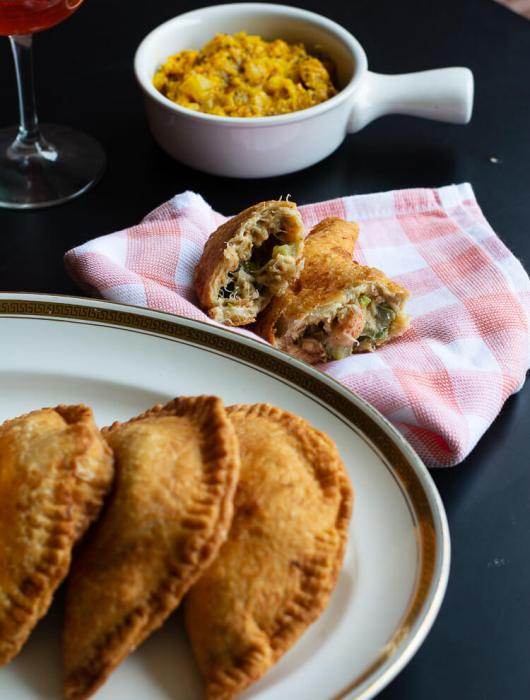 Ghanaian, Savory, Homemade Fried Pies (Seafood stuffed with Crawfish and Crabs) - fried pies served on a white plate with a broken pie on a napkin, and a drink and sauce in the background