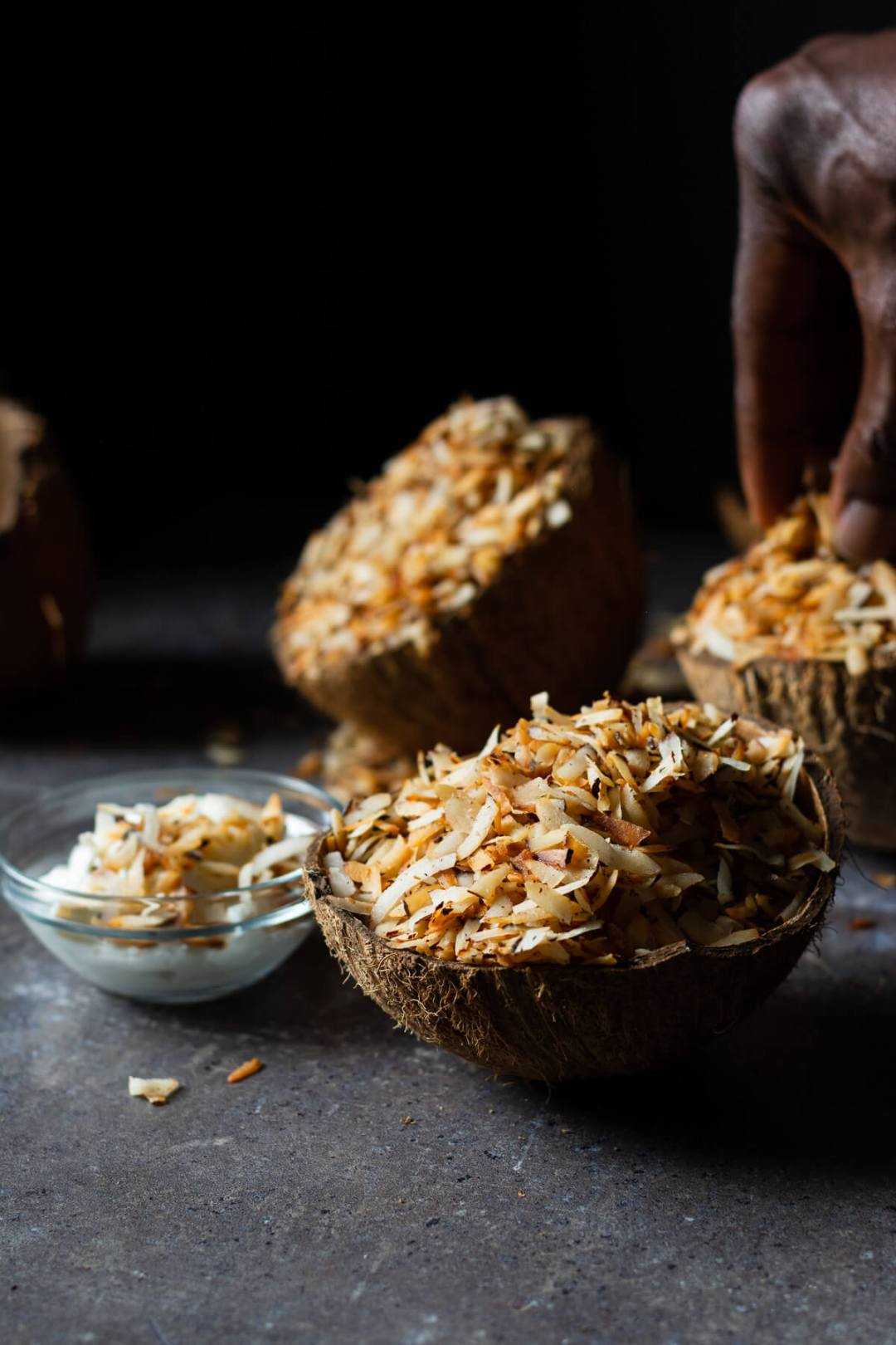 Nigerian coconut candy served in coconut shells with a hand picking some in background