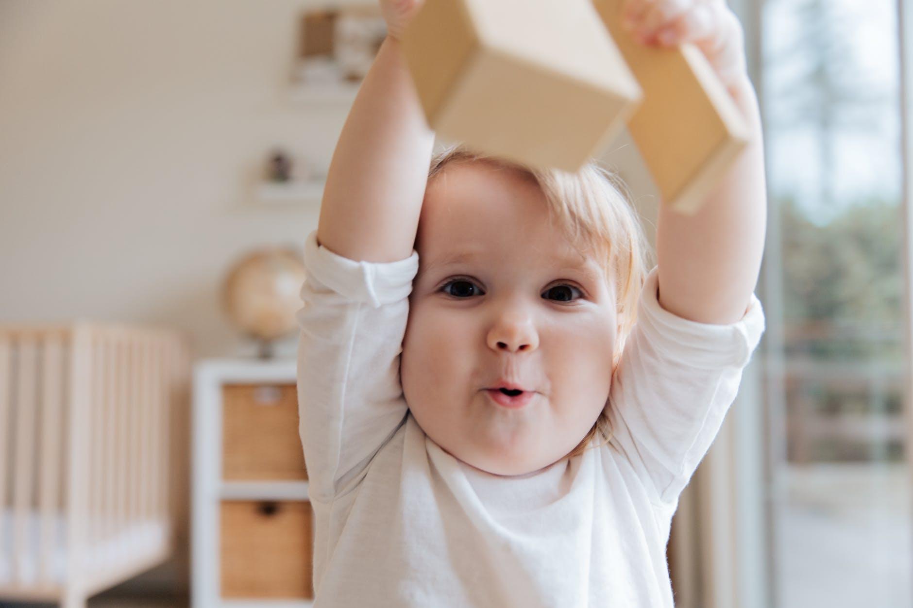 baby in white onesie holding wooden blocks