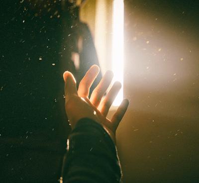 Hand reaching towards light.
