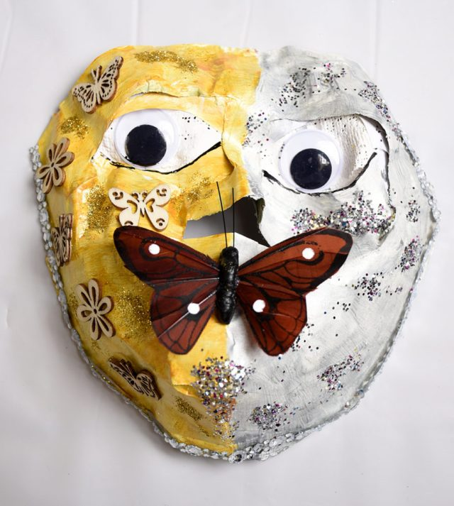 Paper Mache mask featuring a 3-D butterfly as the mouth. The mask is half yellow, decorated with floers and butterflies and half white, decorated with silver sparkles.