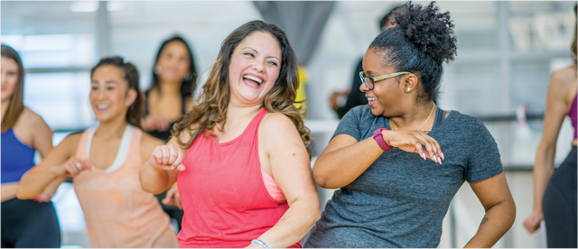 Two women participate in a an exercise dance class. They are laughing and appear to be having fun.