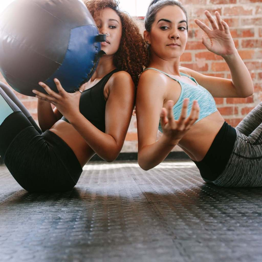 Two sporty women training with medicine ball in gym.