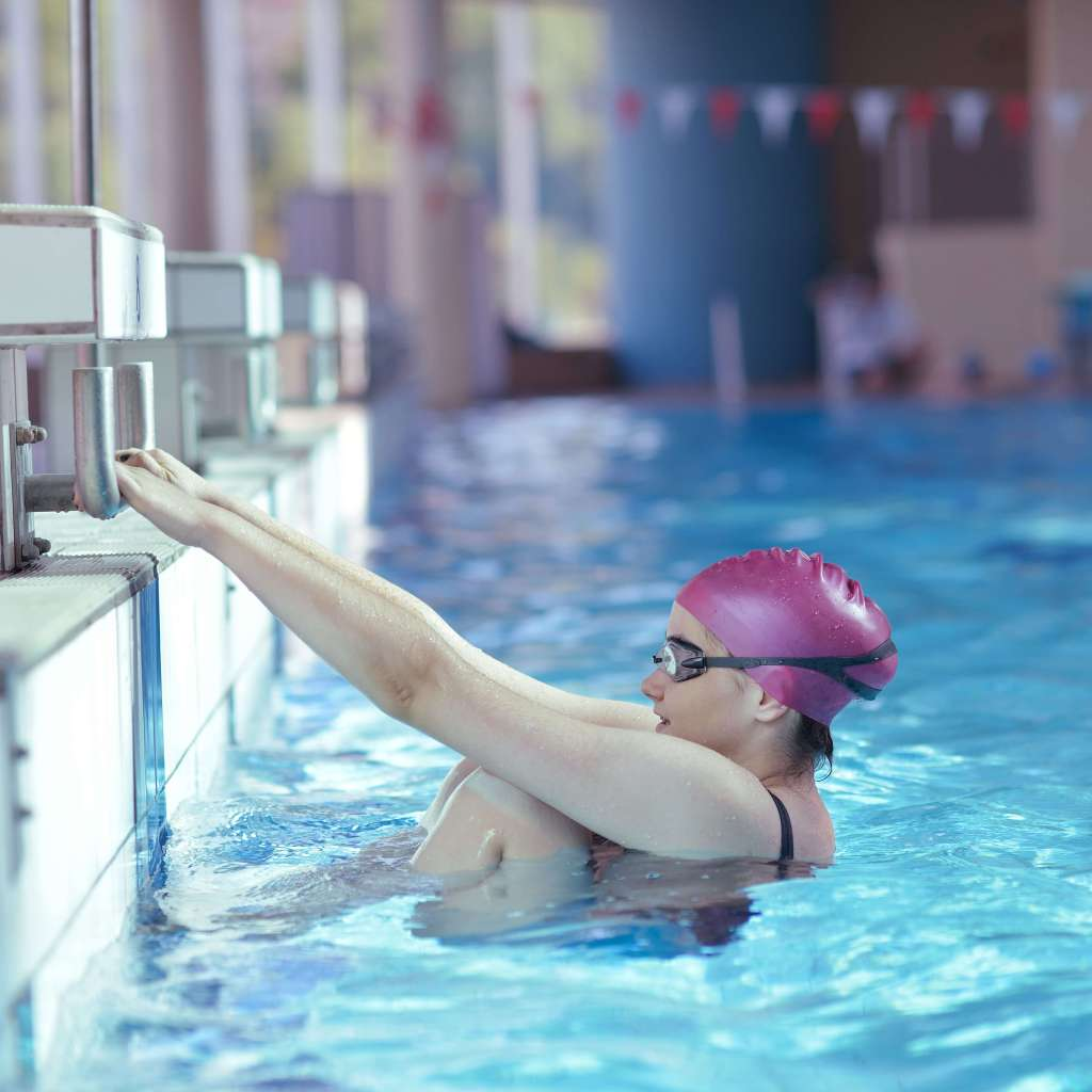 teen girl swimmer prepares to push off from starting block in pool