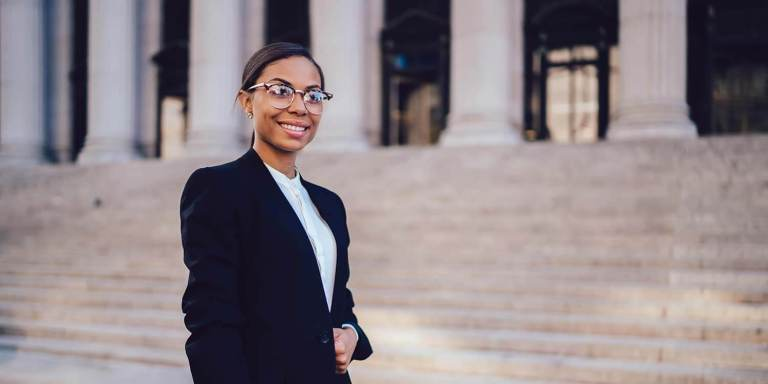 African American woman smiling at camera, wearing formal suit in front of judicial steps