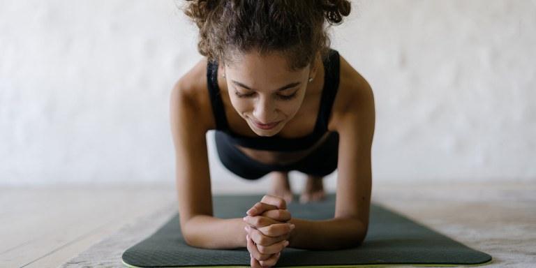 Young Black woman in plank pose on yoga mat against blurred copy space background