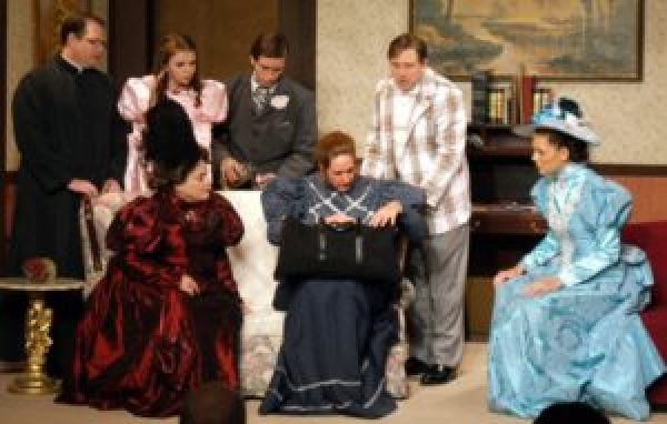 "The principal players in ""The Importance of Being Ernest"" at Theatre 29 gather around a handbag for the play's denouement."