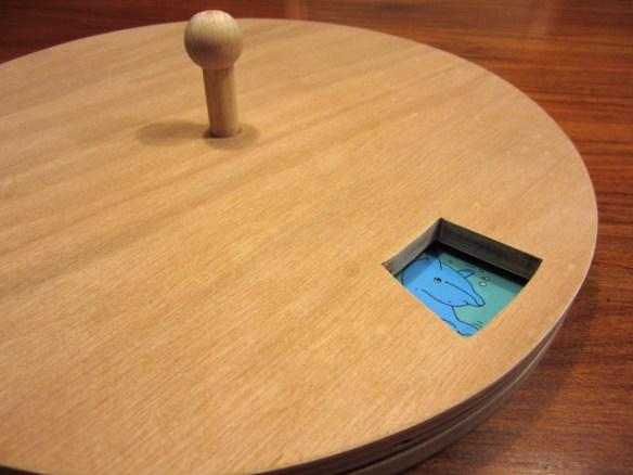 Illustratie: foto van houten draaischijf met een kijkvenster.