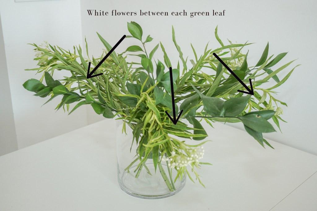 Adding white flowers to vase