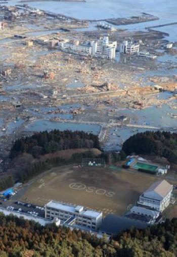 En el patio de una escuela japonesa se pide ayuda (SOS) ante la catástrofe.