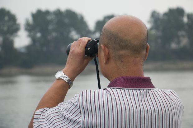 En la ciudad de Dandong, un turista chino utiliza prismáticos para ver lo que pasa al otro lado, en Corea del Norte (FOTO: Daniel Méndez).