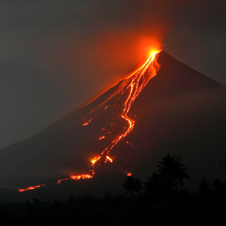 Glowing lava continues to cascade further down the slopes of Mayon volcano on the eve of Christmas Day in Padang town