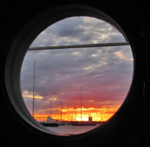A porthole's perspective of the anchorage at sunset.