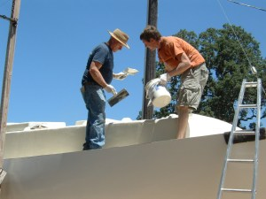 Fairing topsides with the help of a professional drywall finisher.