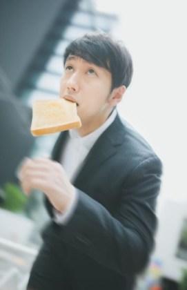 トーストをくわえ、颯爽と出社するビジネスマン