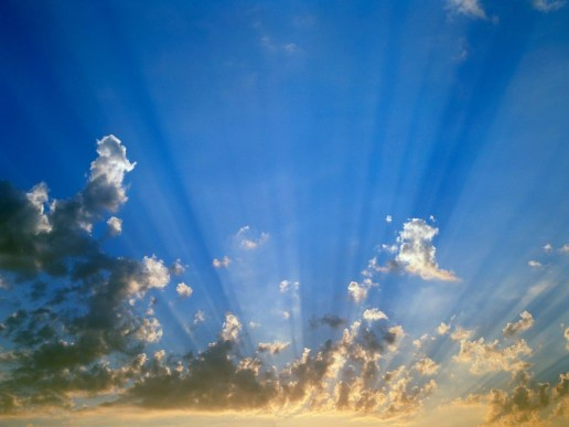 Sunrays and clouds in a blue sky