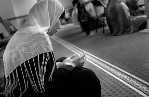 Muslim woman praying, saying dua' in Masjid