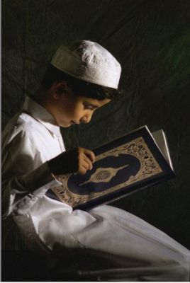 A young Muslim boy reading the Quran