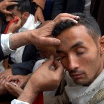 Sanaa, Yemen: Cosmetic Kohl is applied to the eyelids of a young man during Ramadan. Oral traditions relating to the words and deeds of the Prophet Muhammad (pbuh) mention the use of Kohl frequently.