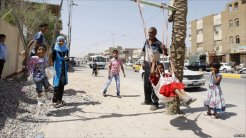 Iraqi children in Basra play on a makeshift swing during the Eid holiday
