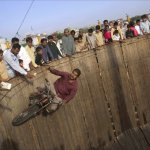 Khalid Raban of Rawalpindi, 43, rides his motorcycle on a vertical track as fans watch