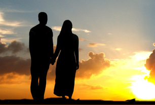 Happy couple silhouetted against the sunset