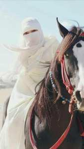Muslim woman in white on horseback