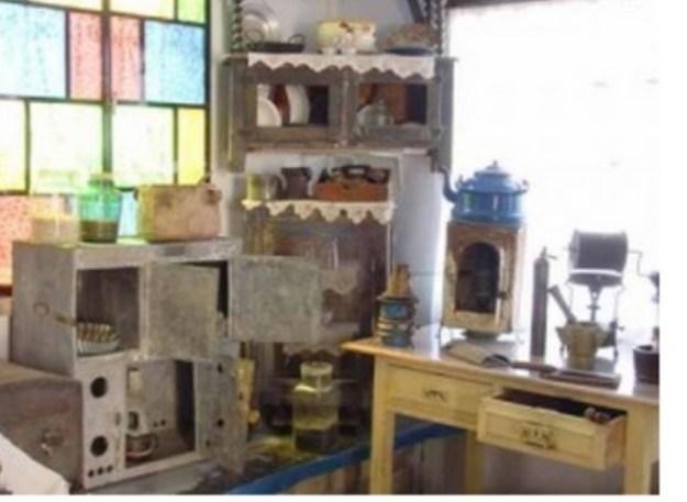תצוגה של מטבח צפתי בבית המאירי. משמאל תנור הפטנט. באמצע תנור פח פשוט ובתוכו עששי ועליו קומקום. מימין מכשיר לקליית קפה מעל פרימוס [המוסתר על ידי מכתש ועלי]