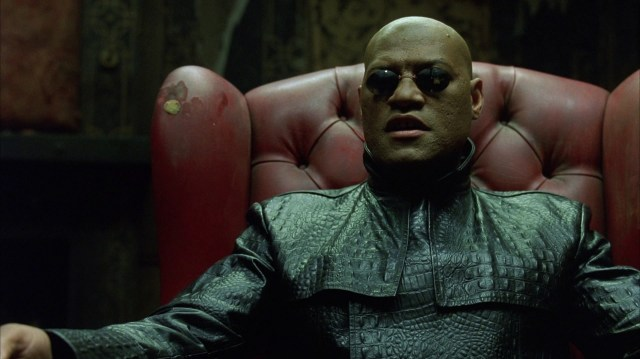 "Morpheus (from ""The Matrix"") seated in a leather chair in a dark room."