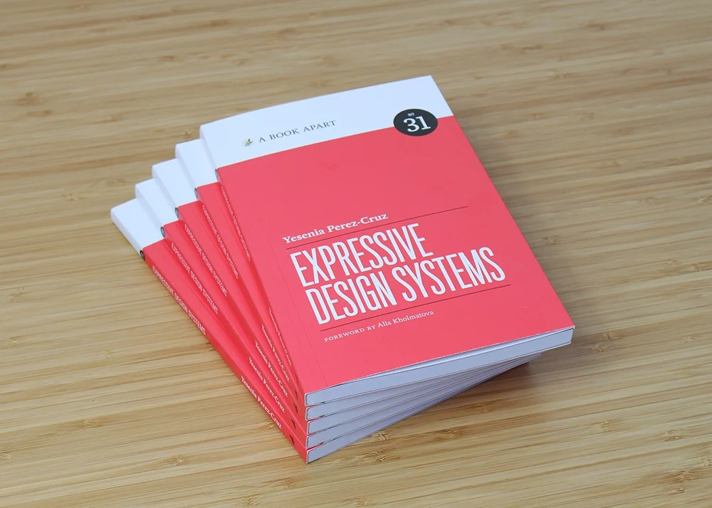 Stacked copies of Expressive Design Systems by Yesenia Perez-Cruz, photographed on a wooden table top.