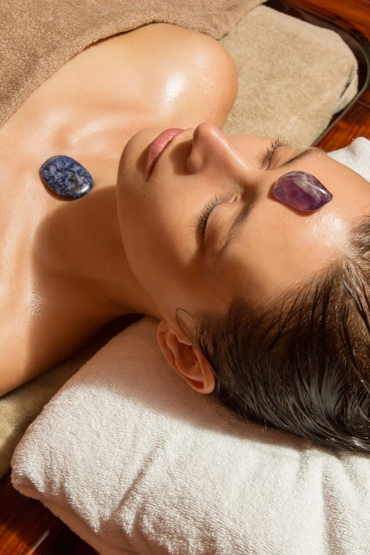 Women with healing crystals on chakras