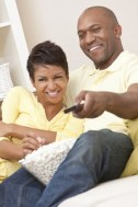 A couple laughing together while watching TV