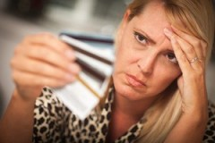 Upset Woman Glaring At Her Many Credit Cards.