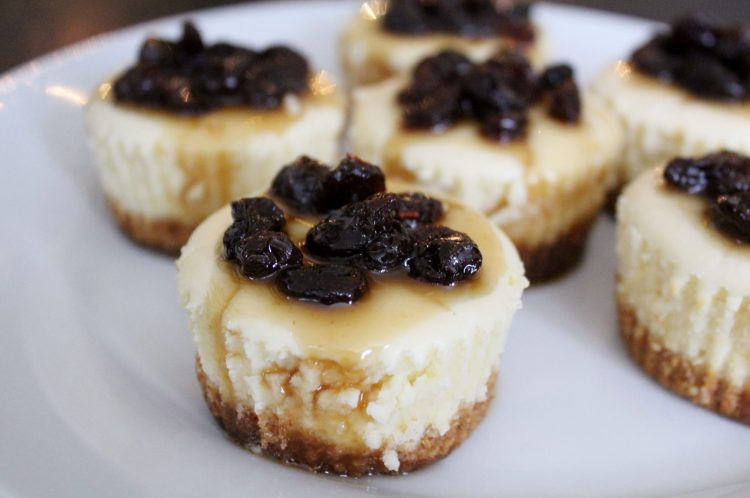 Mini Butter Tart Cheesecakes - All of the goodness of the classic butter tart in creamy cheesecake form! Luscious vanilla cheesecake with a graham cracker crust is topped with decadent maple butter tart sauce, all served in individual portions, making these the perfect portable dessert for holiday entertaining.