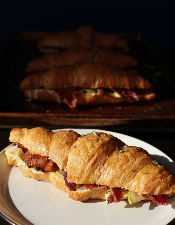 Apple Cheddar Bacon Breakfast Sandwich - sharp cheddar, crispy bacon and apple slices served on a croissant brushed with thyme infused butter. These sweet and savory flavours are a mouthwatering and decadent way to begin your day!
