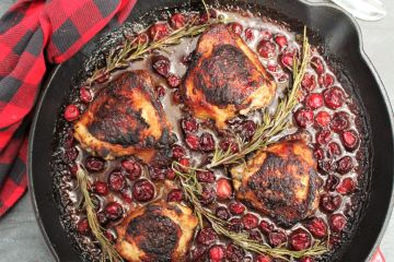 A red cast iron skillet with cranberry rosemary chicken thighs. A red plaid dish towel is wrapped around the handle of the skillet, and a large silver spoon is above.