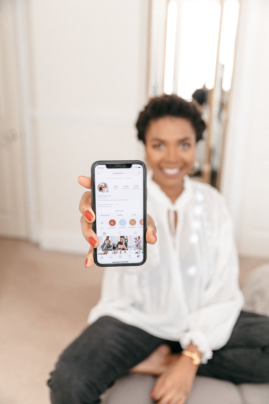 woman sitting down showing instagram profile on iPhone lifestyle blog