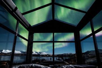 Ammirare l'aurora boreale in Islanda disteso su un comodo letto