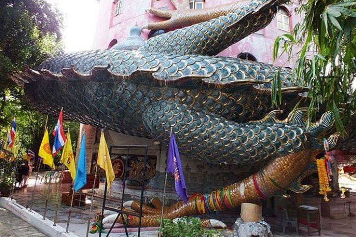 Una torre di un tempio buddista avvolto dalle spire di un drago