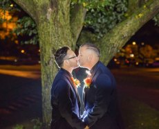 Happy Couple Kissing Under Tree at Wedding