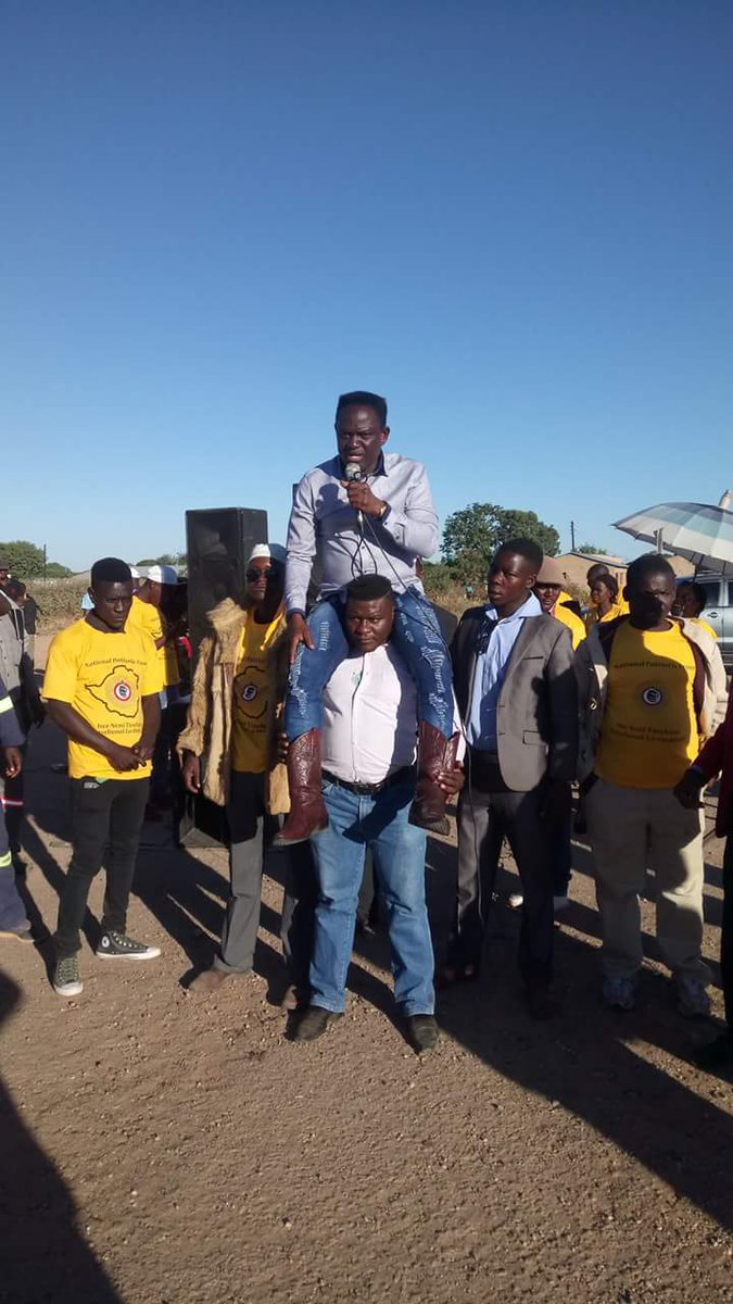 FIRED ZANU PF MP RALLY PULLS A FIRST AS HE SITS ON BODYGUARD WHILE ADDRESSING
