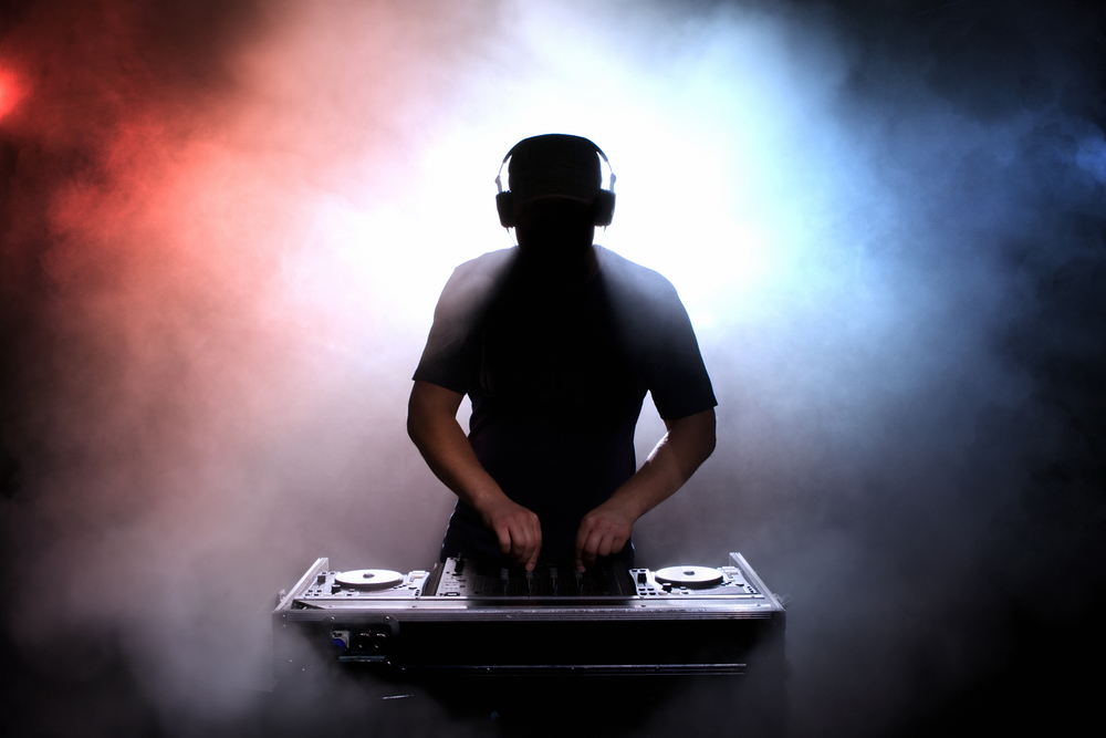 Silhouetted DJ at mixing deck