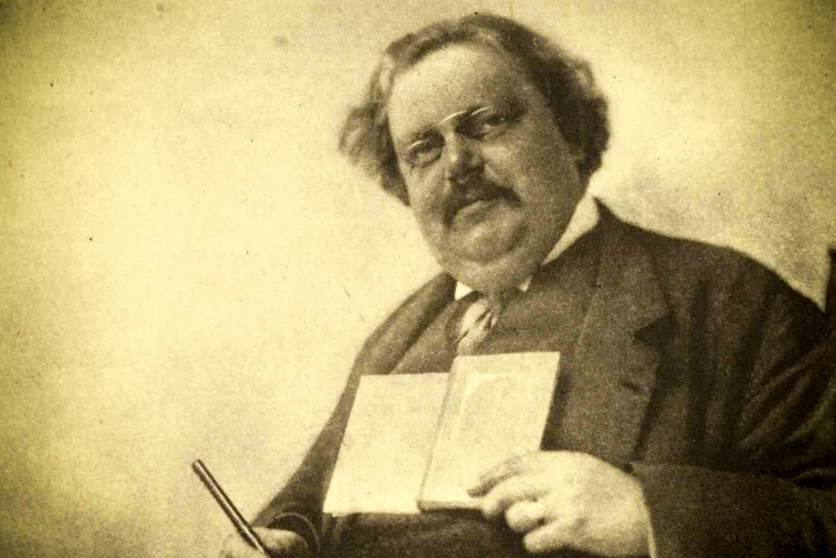 web-gk-chesterton-holding-book-pen-hector-murchison-public-domain-via-wikipedia