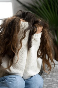 A woman sitted down holding her hair