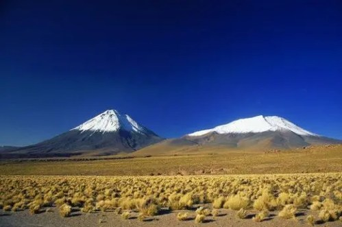 White-peaked volcanos rise from the plains of the Atacama Desert under deep blue skies. The Atacama is the driest desert in the world.