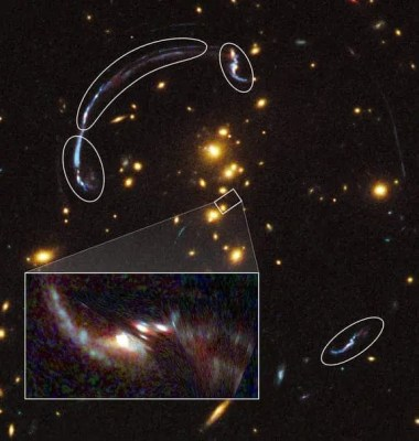 The zoom in rectangle shows the brightest galaxy so far found through a gravity lens. It's 20 times larger and over three times brighter than typically lensed galaxies.The rounded outlines that form an arc are actually the remnant distortions discussed in the article. (c) NASA