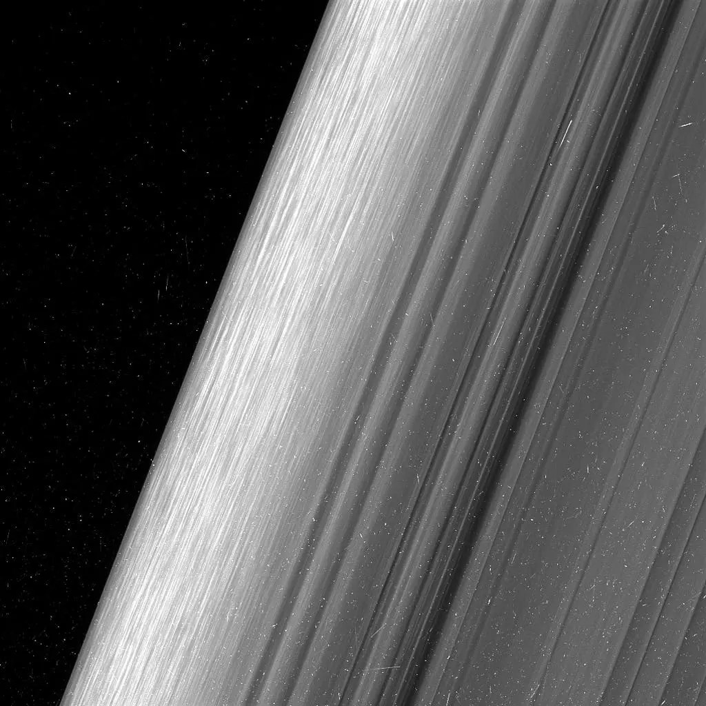 """The view here is of the outer edge of the B ring, at left, which is perturbed by the most powerful gravitational resonance in the rings: the """"2:1 resonance"""" with the icy moon Mimas. This means that, for every single orbit of Mimas, the ring particles at this specific distance from Saturn orbit the planet twice. This results in a regular tugging force that perturbs the particles in this location. Credit: NASA."""