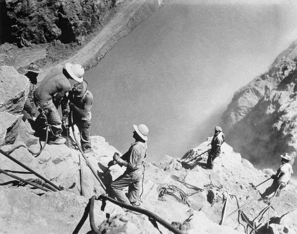 To make sure the canyon walls were solid enough to support the arch design, so-called 'high scalers' were employed to hammer away anything loose. Falling rocks were a serious hazard so the workers dripped their hats in tar and left them out to dry. Essentially, these were some of the first hard hats. Credit: Corbis