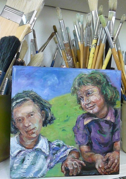 A painting on a wooden box of two friends playing with a hill and sky behind them